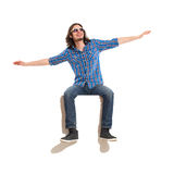 I believe i can fly. Young man sitting on a banner with arms outstretched and looking away. Full length studio shot isolated on white stock image