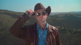 I bergen piskar en man i en cowboyhatt, omslaget, exponeringsglas En man trycker p? hans hatt med hans hand arkivfilmer