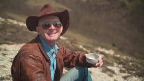 I bergen piskar en man i en cowboyhatt, omslaget, jeans och exponeringsglas Mannen ser ramen och leendena stock video