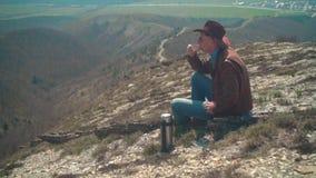 I bergen sitter en man i en cowboyhatt, piskar omslaget, jeans och exponeringsglas E lager videofilmer
