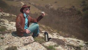 I bergen sitter en man i en cowboyhatt, piskar omslaget, jeans och exponeringsglas E stock video
