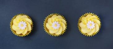 I bigné del limone con il turbinio ed il fondente della crema del burro fioriscono la decorazione Fotografia Stock Libera da Diritti