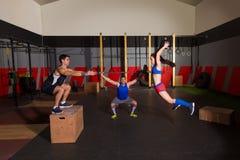 I bilancieri di allenamento del gruppo della palestra sbattono le palle e saltano Immagini Stock