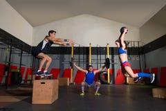 I bilancieri di allenamento del gruppo della palestra sbattono le palle e saltano Fotografie Stock