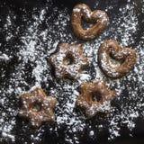 I biscotti bavaresi hanno ghiacciato con la polvere dello zucchero sui precedenti neri Immagini Stock