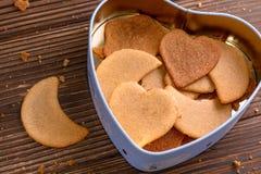 I biscotti casalinghi dello zenzero nel cuore hanno modellato la scatola su fondo di legno fotografie stock