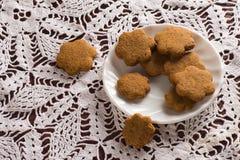 I biscotti del miele sopra lavorano all'uncinetto la tovaglia Immagine Stock