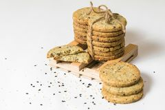 I biscotti del sesamo accatastano con cordicella rustica isolata su fondo bianco Copi lo spazio fotografia stock