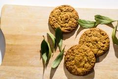 I biscotti dell'avena sulla tavola di legno con la baia va Fotografia Stock