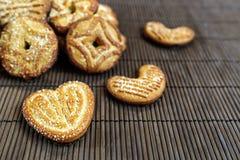 I biscotti dolci dello zucchero un cuore hanno modellato gli scorrevoli su un pelo di bambù marrone Immagine Stock Libera da Diritti