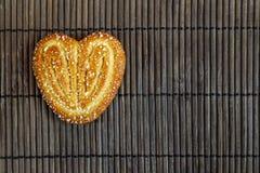 I biscotti dolci dello zucchero un cuore hanno modellato gli scorrevoli su un pelo di bambù marrone Fotografia Stock