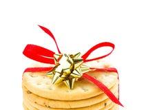 I biscotti dolci di Natale legati con il nastro rosso solated sulla b bianca Fotografia Stock