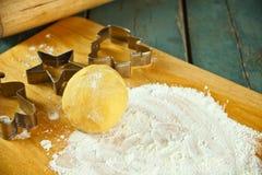 I biscotti e la taglierina non cotti del biscotto si forma sulla tavola Immagine Stock