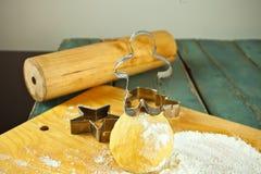 I biscotti e la taglierina non cotti del biscotto si forma sulla tavola Fotografia Stock