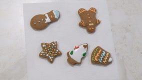 I biscotti festivi colorati del pan di zenzero si trovano su un tovagliolo Biscotti di natale Tabella bianca archivi video