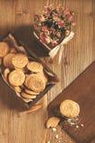 I biscotti rotondi dentro wooben la scatola, le briciole e le rose asciutte Immagine Stock