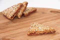 I biscotti triangolari con le ciliege su un bordo di legno della cucina Fotografia Stock