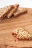 I biscotti triangolari con le ciliege su un bordo di legno della cucina Immagini Stock