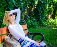 I bisogni di signora si rilassano e vacation La ragazza si siede il banco che si rilassa nell'ombra, fondo verde della natura Vac fotografia stock libera da diritti