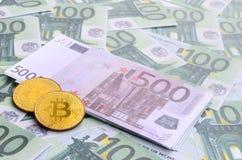 I bitcoins fisici dorati è bugie su un insieme del deno monetario verde Immagini Stock