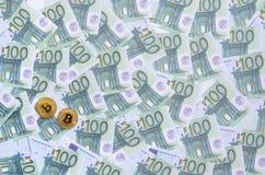 I bitcoins fisici dorati è bugie su un insieme del deno monetario verde Fotografia Stock Libera da Diritti