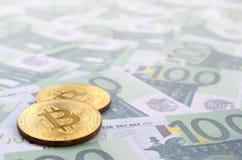 I bitcoins fisici dorati è bugie su un insieme del deno monetario verde Fotografie Stock