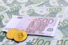 I bitcoins fisici dorati è bugie su un insieme del deno monetario verde Fotografia Stock