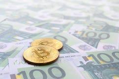 I bitcoins fisici dorati è bugie su un insieme del deno monetario verde Fotografie Stock Libere da Diritti