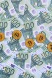 I bitcoins fisici dorati è bugie su un insieme del deno monetario verde Immagini Stock Libere da Diritti