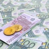 I bitcoins fisici dorati è bugie su un insieme del deno monetario verde Immagine Stock