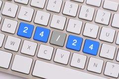 24/24 i blått på det vita tangentbordet Arkivfoto
