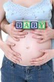 I blocchetti di alfabeto hanno tenuto prevedendo i genitori sopra la pancia della mamma Fotografia Stock Libera da Diritti
