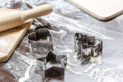 I bordi di legno, la farina e le taglierine del biscotto sotto forma del ` dell'albero di Natale del ` del ` del cuore del `, del Immagine Stock