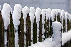 I bordi grigi di legno vecchi recintano la neve bianca Fotografia Stock