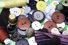 I bottoni, i fili ed il ditale sono sulla tavola immagine stock