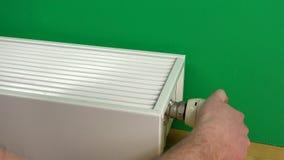 I braccia maschii dell'uomo aumentano la temperatura del radiatore e le mani calde  video d archivio