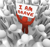 I Am Brave Man Person Holding Sign Courage Daring Bold Action. I Am Brave words on a sign held by one man in a crowd showing he is unique and different in being Stock Photos
