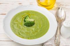 I broccoli scremano la minestra con olio d'oliva in un piatto bianco Fotografie Stock