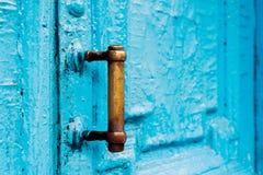 I buchi della serratura del primo piano con le tende e una maniglia sul blu molte volte hanno dipinto la porta d'annata di legno  Fotografia Stock