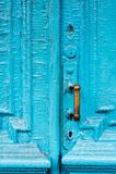 I buchi della serratura del primo piano con le tende e una maniglia sul blu molte volte hanno dipinto la porta d'annata di legno  Immagine Stock