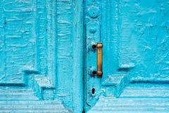I buchi della serratura del primo piano con le tende e una maniglia sul blu molte volte hanno dipinto la porta d'annata di legno  Fotografie Stock Libere da Diritti