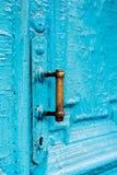 I buchi della serratura del primo piano con le tende e una maniglia sul blu molte volte hanno dipinto la porta d'annata di legno  Fotografie Stock