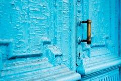 I buchi della serratura del primo piano con le tende e una maniglia sul blu molte volte hanno dipinto la porta d'annata di legno  Immagine Stock Libera da Diritti