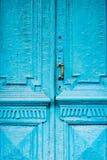 I buchi della serratura del primo piano con le tende e una maniglia sul blu molte volte hanno dipinto la porta d'annata di legno  Immagini Stock