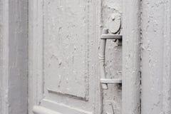 I buchi della serratura del primo piano con le tende e una maniglia sul gray molte volte hanno dipinto la porta d'annata di legno Fotografia Stock Libera da Diritti