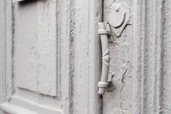 I buchi della serratura del primo piano con le tende e una maniglia sul gray molte volte hanno dipinto la porta d'annata di legno Fotografia Stock