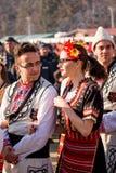 I bulgariska folk dräkter och att se sig arkivbilder