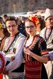 I bulgariska folkloredräkter och att tycka om det Arkivfoto