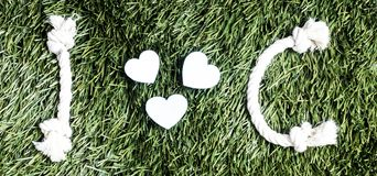I and C letters and three paper heart cut outs on grass.  Stock Photography