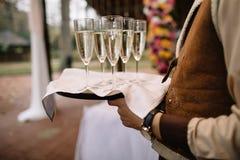 I camerieri accolgono gli ospiti con le bevande alcoliche Champagne, w rosso fotografia stock libera da diritti